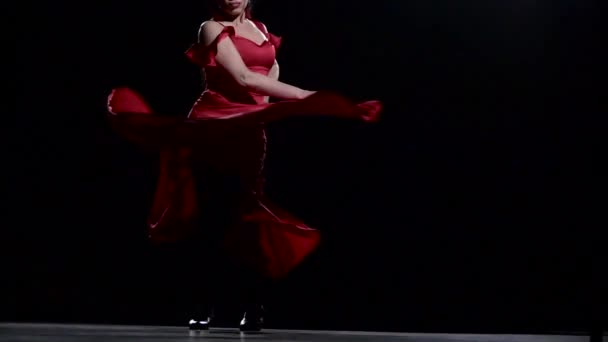Girl is spinning in a red dress. Black background. Slow motion