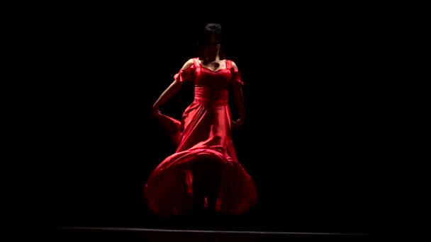 Girl in a red dress is dancing the sexual movements of a flamenco dance. Black background. Slow motion