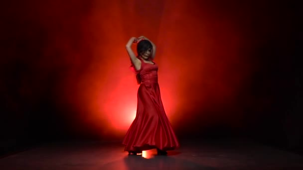 Girl in an incendiary dance of flamenco . Llight from behind. Smoke background. Slow motion