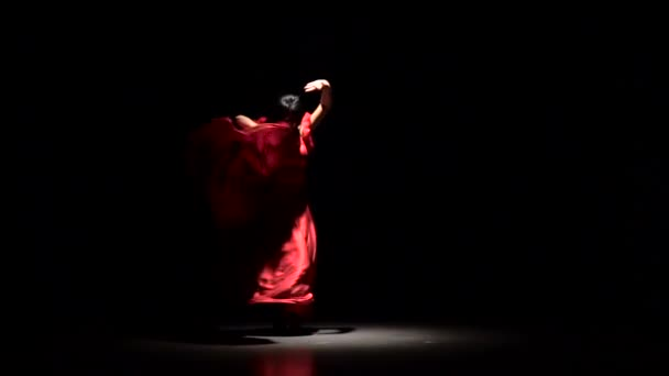 Girl in dress the dark room performs elegant movements with her hands in dance. Black background. Slow motion