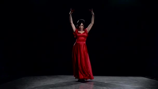 Women the dark room performs elegant movements with her hands in sexual dance. Black background. Slow motion