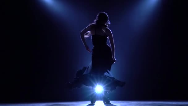Girl is dancing in a dark room with graceful hand movements. Llight from behind. Smoke background. Silhouette. Slow motion