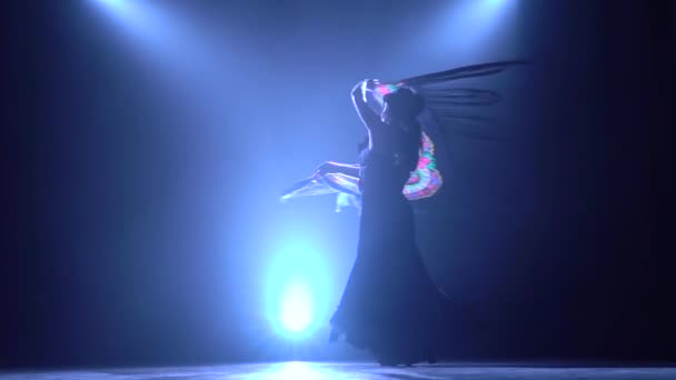 Dancing woman is with a manton in the hands of a Spanish incendiary dance. Llight from behind. Smoke background. Silhouette. Slow motion