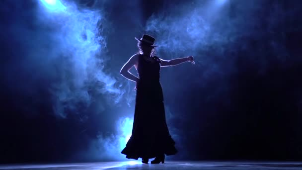 Flamenco. Woman in a chic dress turns in an incendiary dance . Llight from behind. Smoke background. Silhouette. Slow motion