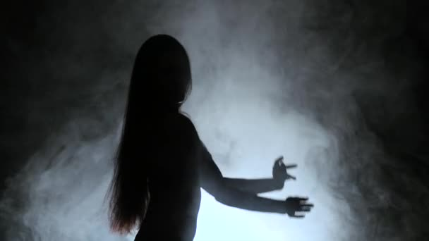 Girl is dancing a sexy dance in the smoke. Black background. Silhouette