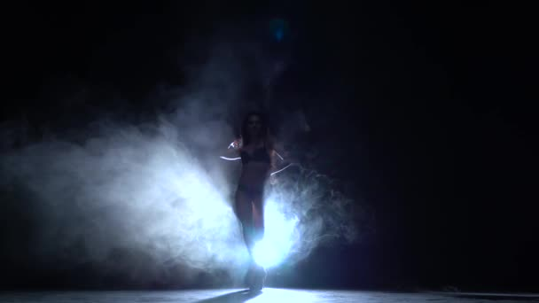 Girl dances erotic movements. Black smoke background. Silhouette