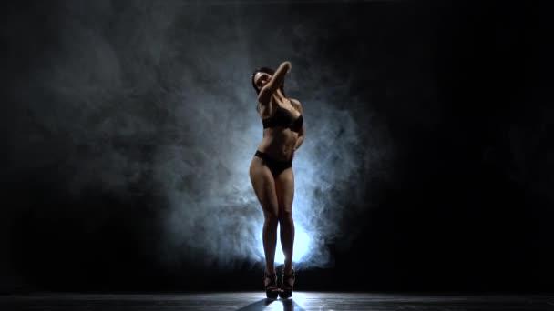 Striptease with a sexy body. Black smoke background