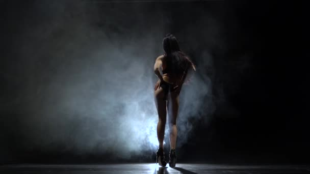 Girl in heels dancing sexual dance. Black smoke background