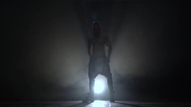Muž, tančí eroticky. Na pozadí černého kouře. Silueta