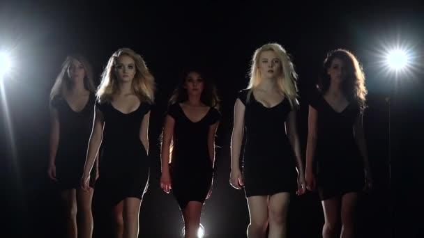 Model chůzí krásných dívek. Černé pozadí. Zpomalený pohyb