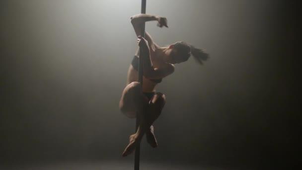 Mädchen tanzt Poledance. Schwarzer Hintergrund. Slow-motion