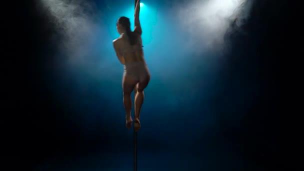 Girl dancing erotic dance in the dark with smoke and blue spotlights. Black smoke background