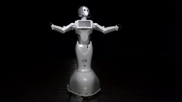 Robot mluví a provádí pohyby. Černé pozadí