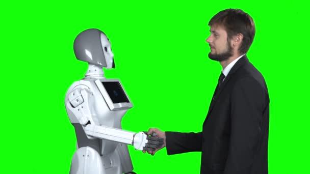 Robot kezet egy férfival köszön neki. Zöld képernyő