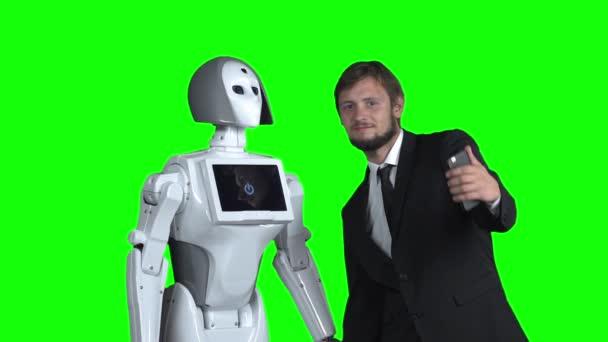 Chlap s robotem je fotografoval a focení. Zelená obrazovka. Zpomalený pohyb