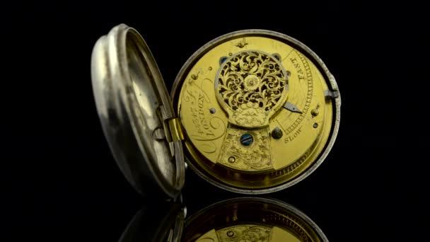Meccanismo di orologio antico che funziona. Sfondo nero. Suono