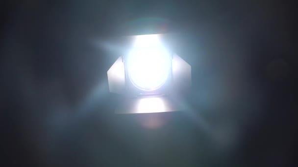 Reflektory v tmavé studio se rozsvítí a zhasne. Černé pozadí
