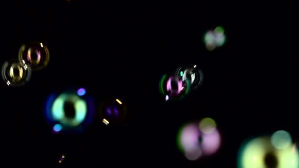 Mýdlové bubliny fly a praskla ve vzduchu. Zpomalený pohyb. Černé pozadí