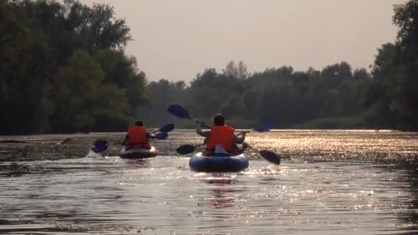 Shot of kayakers kayaking down the river i on a sunset day
