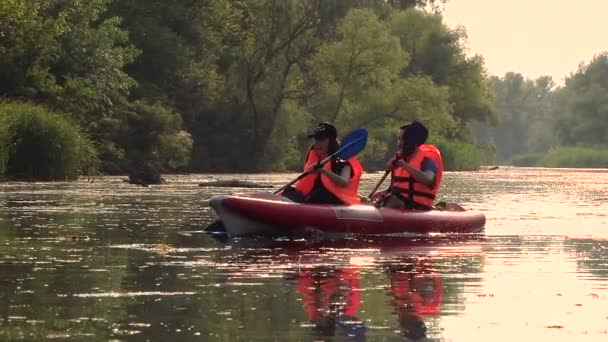 Kayak with a guy and a girl swims on the river. Slow motion