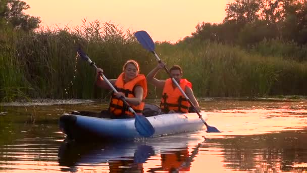 Two people in rowing oars sitting in a kayak on the lake in the sunset. Slow motion
