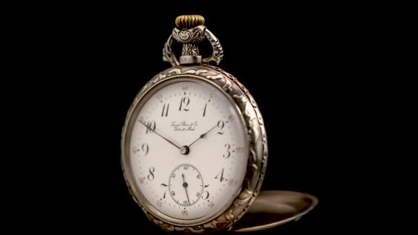 Vintage pocket watch rotate arrows go. Black background. Time lapse