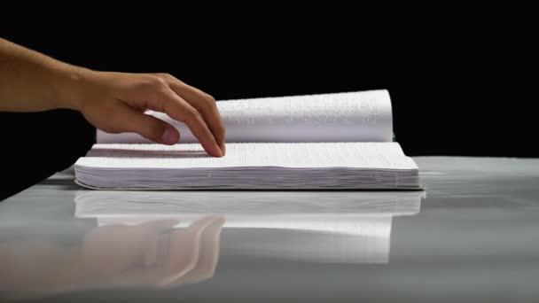 Slepý čtení textu v jazyce Braillova písma. Černé pozadí. Boční pohled