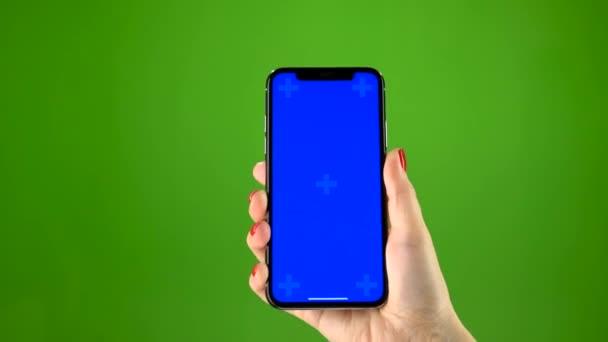 Ženská ruka drží nejnovější smartphone na zelené obrazovce