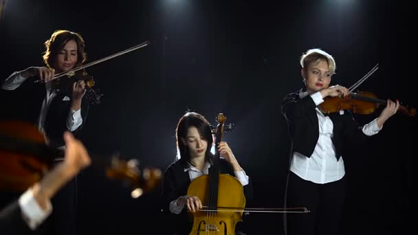 Smyčcový kvartet vystupuje na sólových koncert fázi světlo. Na pozadí černého kouře. Detailní záběr