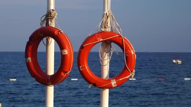 Zwei Rettungsringe hängen an einer Stange im Meer, Menschen baden