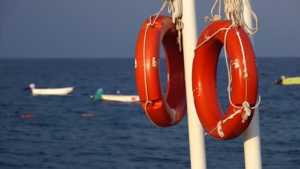 Rettungsringe hängen an der Seebrücke im Meer und schwanken auf den Wellen des Bootes
