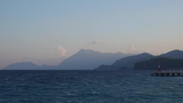Večerní krajina s mořem a horami v pozadí