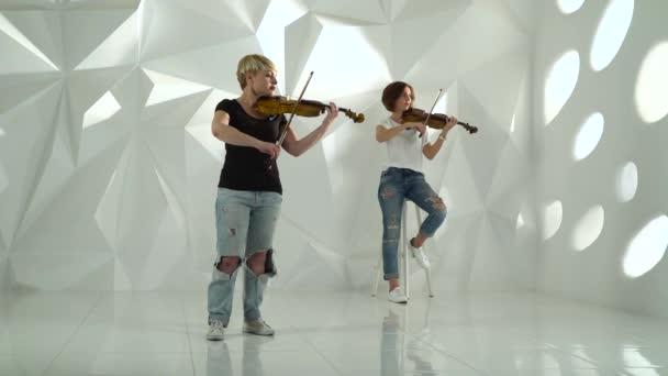 Dívky hrají housle lyrické kompozice stojící v bílé místnosti