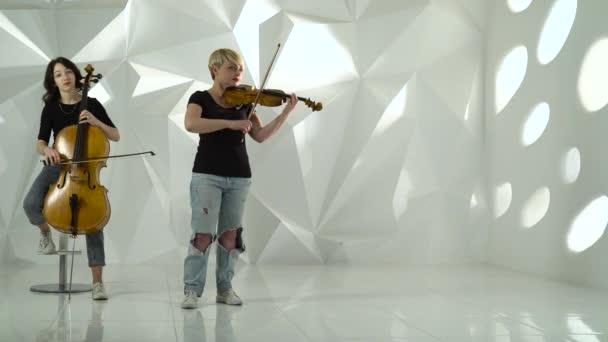 Csellista és hegedűművész játszik egy zenemű