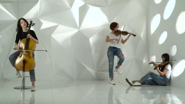 Dvě dívky hrají housle jeden na violoncello v bílé studio