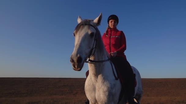 Dívka sedící na koni vypadá do dálky v poli proti obloze. Zpomalený pohyb