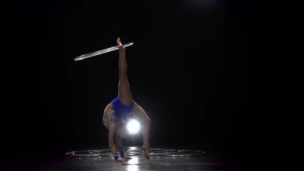Turnerin im hellen Outfit dreht einen Reifen um ihren Arm und dann um ihr Bein. schwarzer Hintergrund