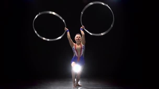 Mädchen-Turnerin dreht die Reifen und Tänze. Schwarzem Hintergrund