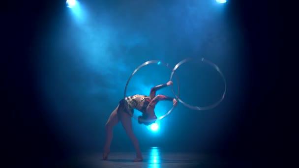 Acrobat-Bewegungen mit Reifen. Blauer Rauch Hintergrund