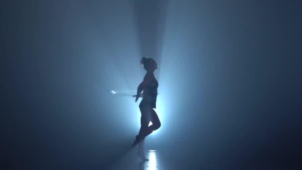 Mädchen Gymnast führt Tricks mit Reifen auf ihre Hände und hebt ihr Bein in der Luft. Hintergrund zu rauchen. Silhouette