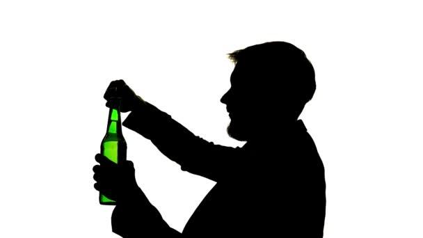 Muž v pokoji sedí otevře a pije z láhve. Boční pohled. Silueta bílé pozadí