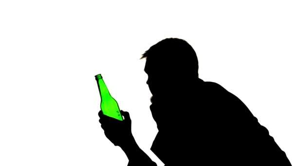 Alkoholik sedí s lahví v ruce a nápoje. Boční pohled. Silueta bílé pozadí