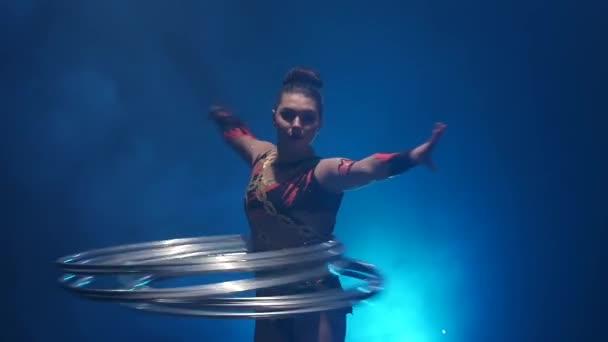 Turnerin mit Reifen dreht sie auf den Körper, Hände, anmutig und attraktiv. Blauer Rauch Hintergrund. Slow-motion
