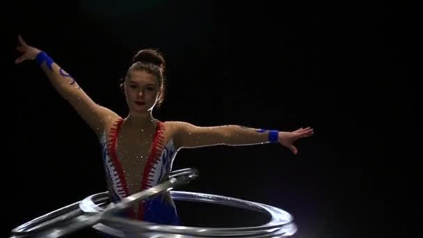 Turnerin dreht am Körper viele Reifen, die sie trainiert. schwarzer Hintergrund. Zeitlupe