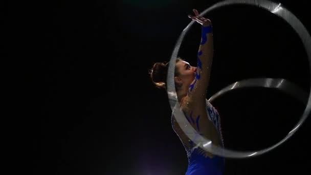 Rhythmische Gymnastik-Mädchen mit Reifen. Schwarzer Hintergrund. Slow-motion