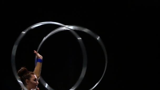 Gymnast dreht an ihren Händen eine Menge von Reifen. Schwarzer Hintergrund. Slow-motion