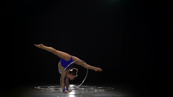 Girl stands on her hands and twists a hoop on her leg. Black background. Slow motion