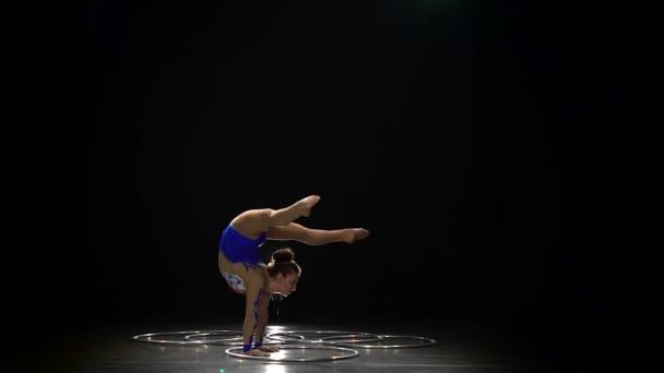 Gymnastka stojí na rukou provádí akrobatické pohyby. Černé pozadí. Zpomalený pohyb