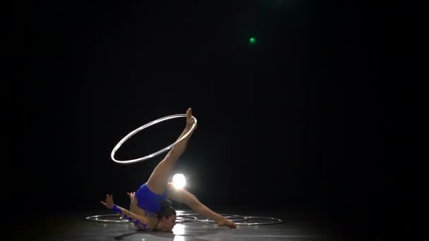 Mädchen turnen mit einem Gymnastikreifen. schwarzer Hintergrund. Zeitlupe