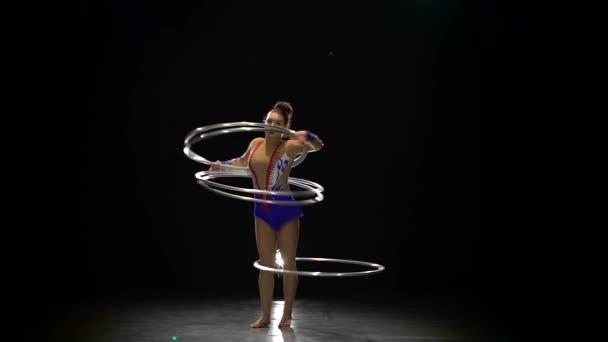 Turnerin dreht in einem Studio die Reifen an ihrem Körper. schwarzer Hintergrund. Zeitlupe